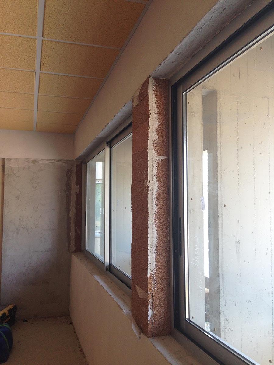 Particolare dell'applicazione dei pannelli in sughero biondo naturale supkompatto SoKoVerd.LV a grana fine 2/3mm sotto il davanzale, spalle finestre e cassonetti per eliminare i ponti termici